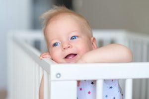 Baby boy standing in crib