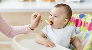 Mom feeding her toddler with fresh organic baby food