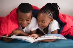 Smiling siblings reading book together while lying on bed