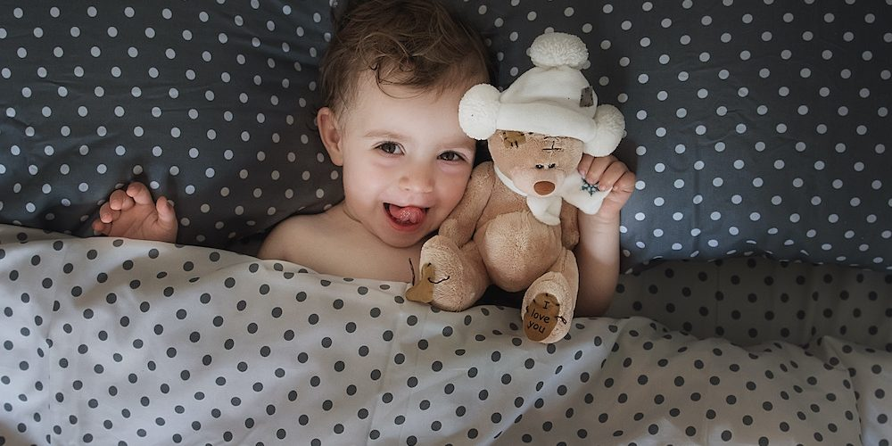 A little girl goes to bed with her favorite toy bear. Happy healthy childhood. Say no to insomnia.